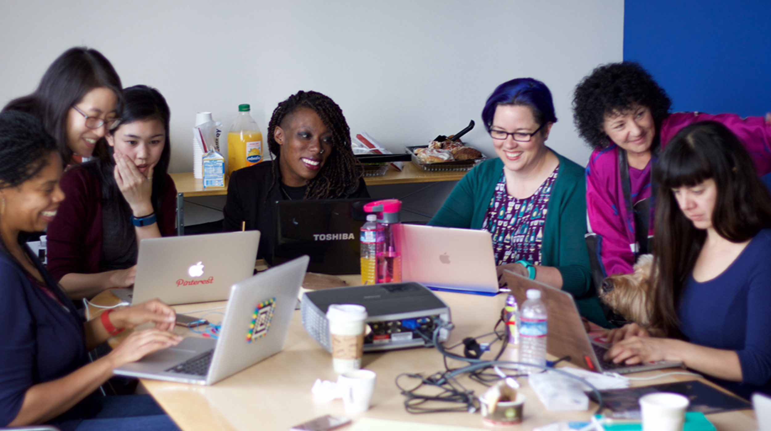 women in tech (image: women sitting at a table on their laptops)