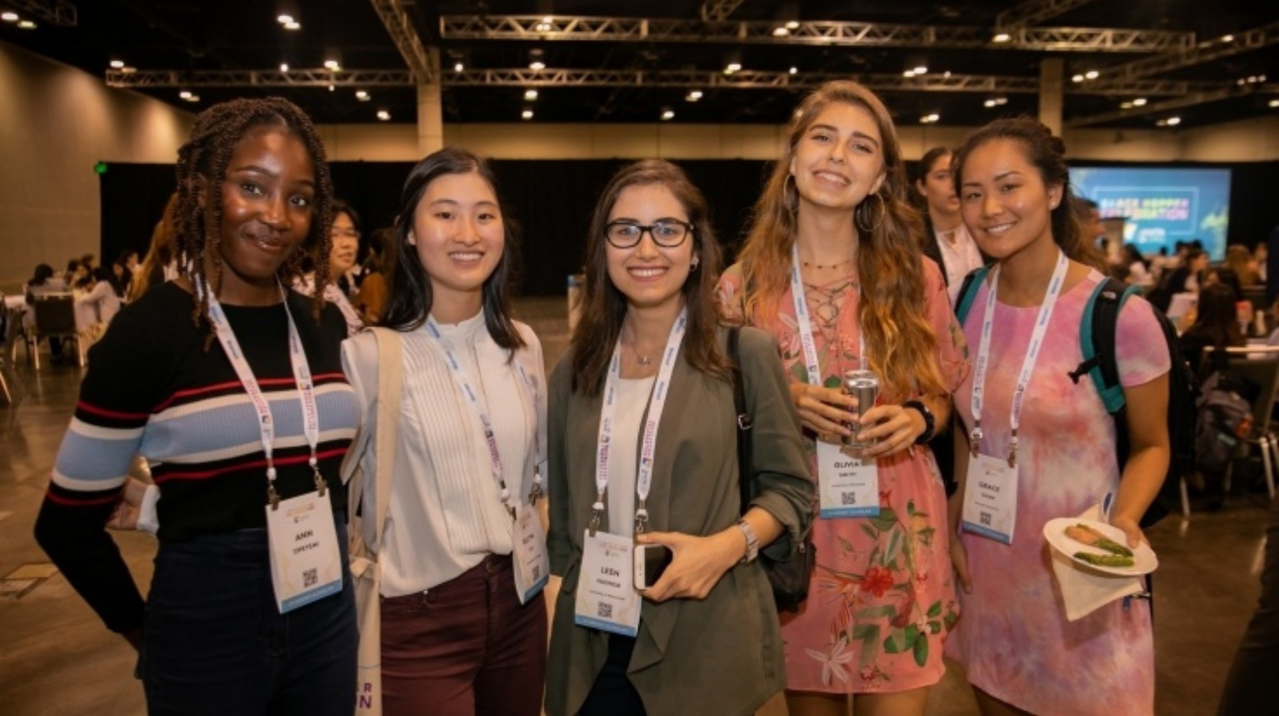 women in tech (image: group of young women at a convention pose for photo)