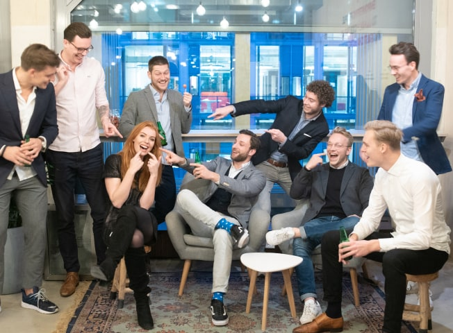 8 men laughing and pointing a woman