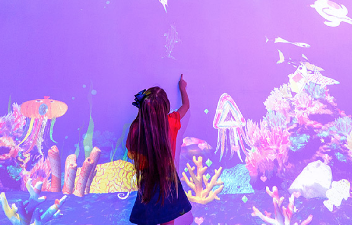 girl pointing wall with an ocean image projected