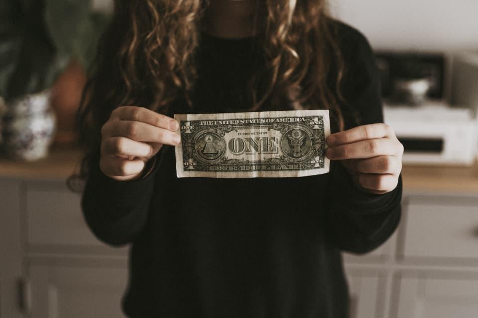 Person holding a dollar bill, by Annie Spratt
