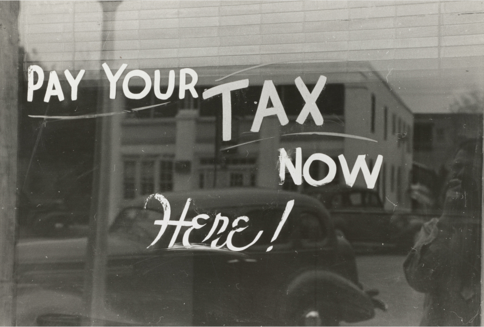 Antique painted window sign that says 'pay your taxes now here!'