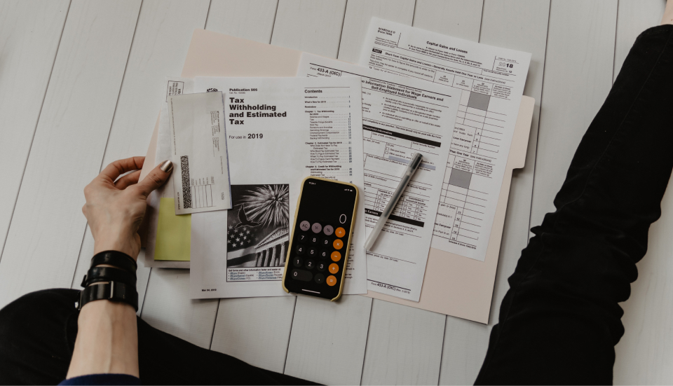 Persons hand holding tax forms and a calculator