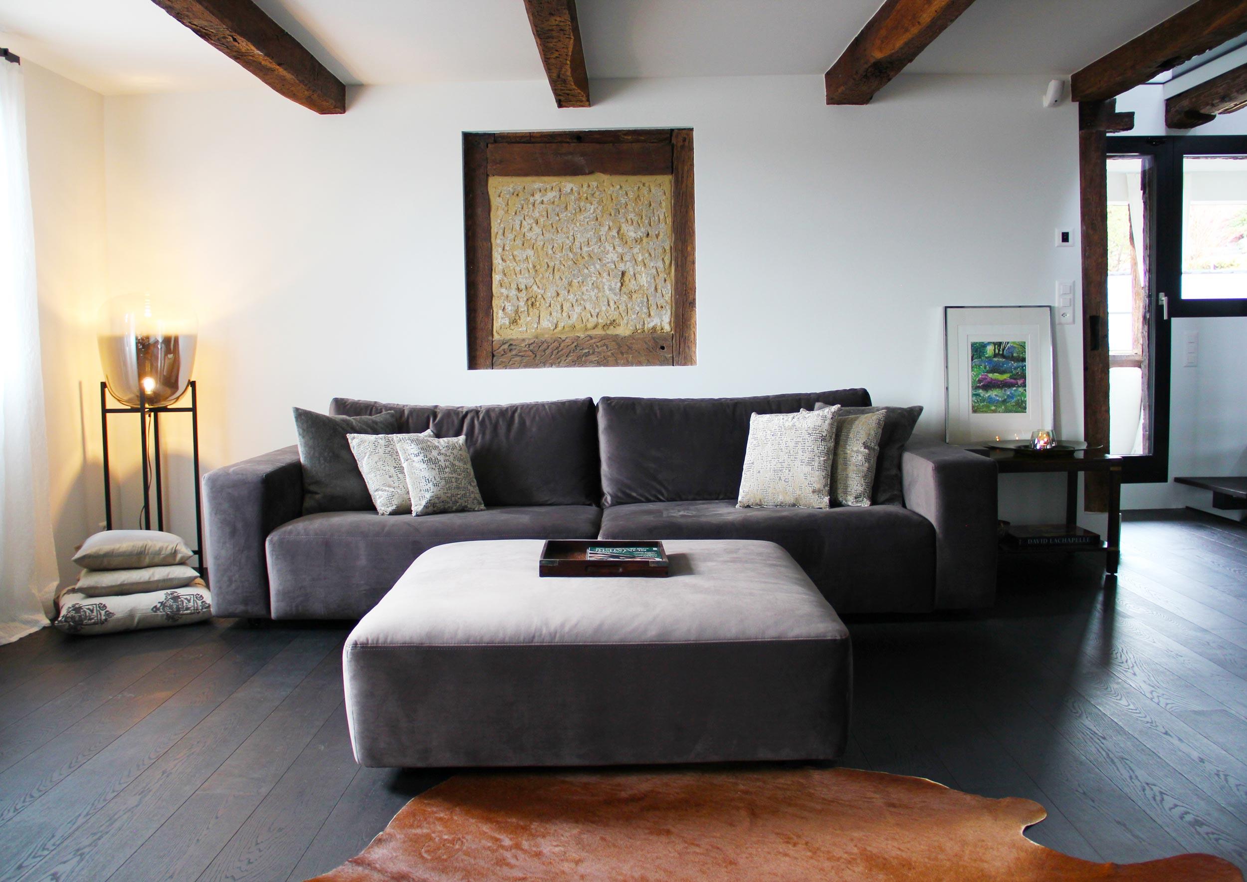 Holzboden, Sichtbalken und  sorgfältig ausgewählte Möbelstücke schaffen Gemütlichkeit im Wohnraum.