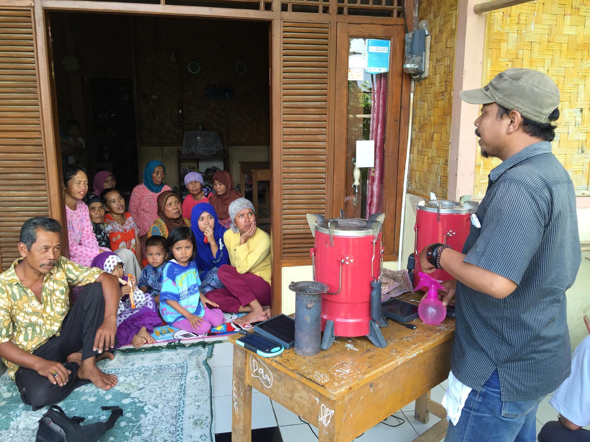Lokale Hersteller instruieren die Familien über die Vorteile ihrer nachhaltigen Produkte. Clean Cooking Alliance