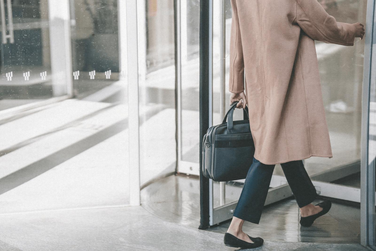 business women walking into revolving door