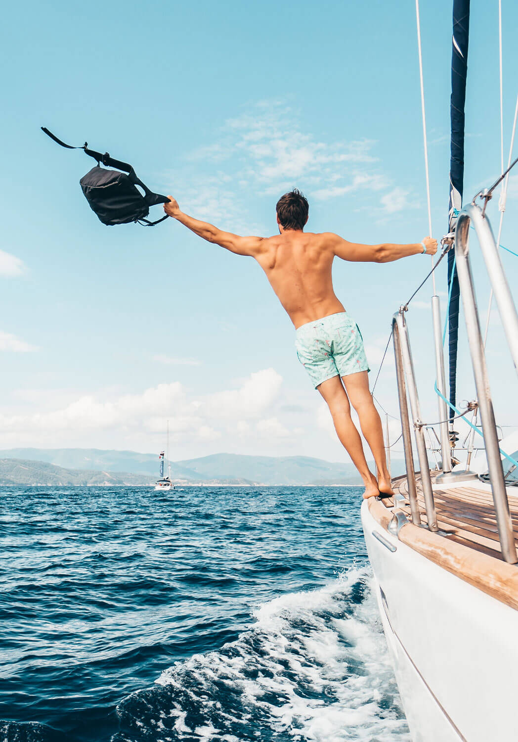 man on a sail boat enjoying life hanging off the side