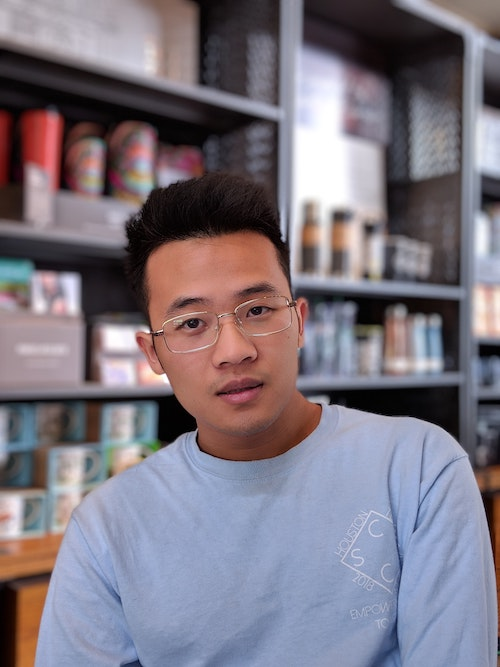 stoic looking man with glasses sitting in front of bookshelf