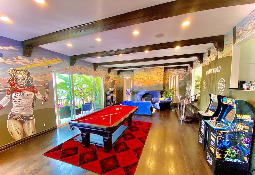 A wide-lense shot of the hhr houses game room with arcade games and pool and a full room mural inspired by Hollywood.