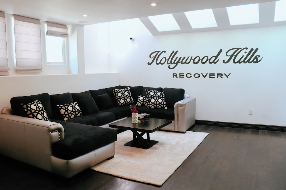 A great shot of the den with a sofa and hollywood hills recovery branding on the white wall.