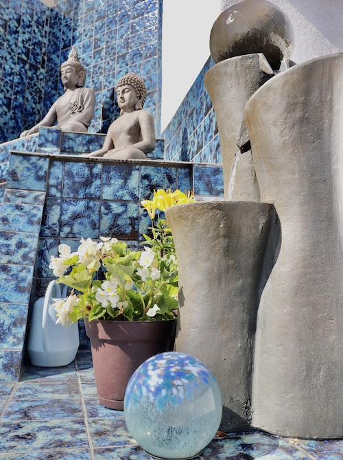 A shot of the staircase at hhr house with decorative Buddha statues and a fountain.