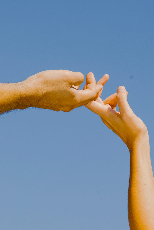Two hands elegantly touch under a blue sky.