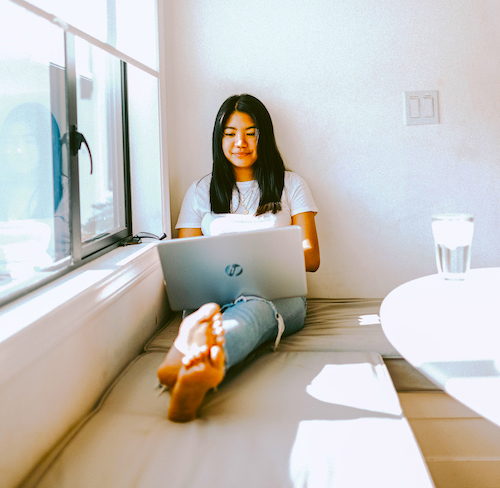 A young woman sits by a window seal with her legs crossed as she works on her laptop.