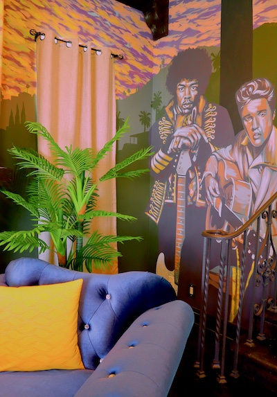 An angular shot of the chessboard in the game room with a blue sofa behind it and a mural of Jimi Hendrix on the wall in the back.