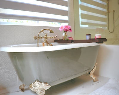 A beautiful vintage tub with gold brass and pink flowers on the try.