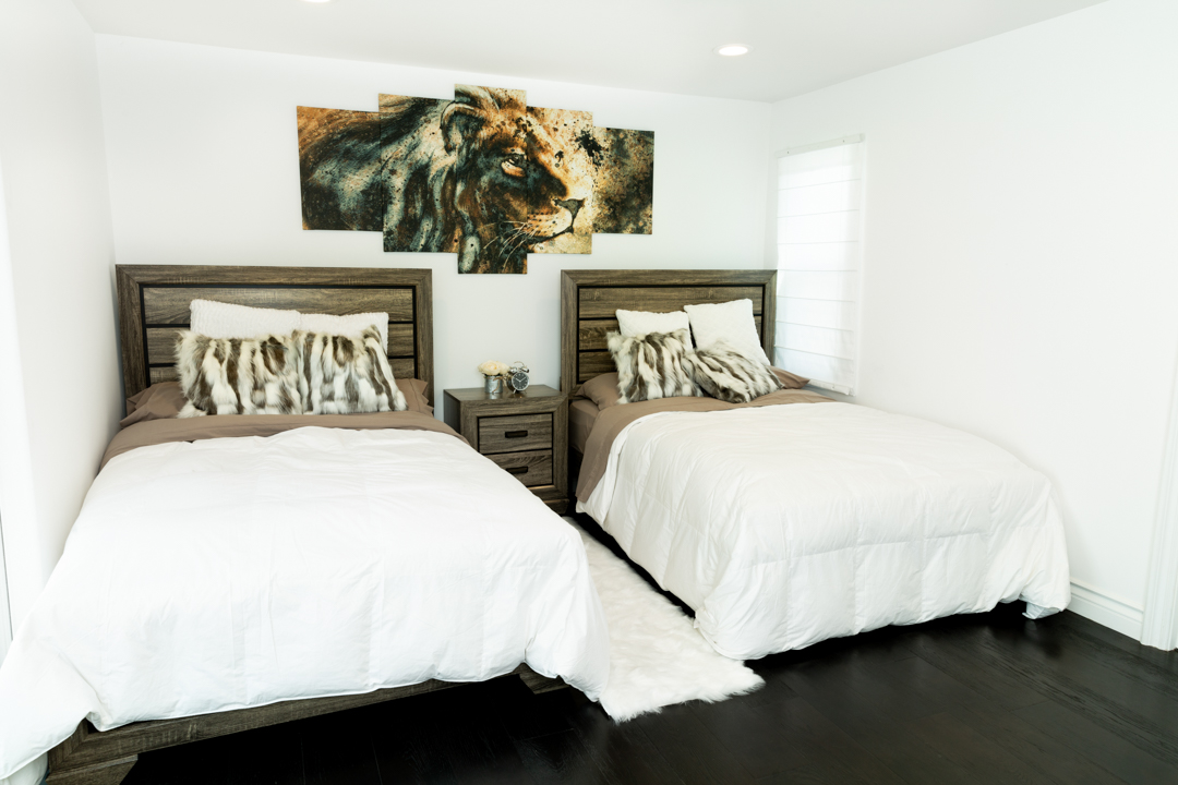 A shot of a bedroom with two bets and a lion picture on the wall inbetween.