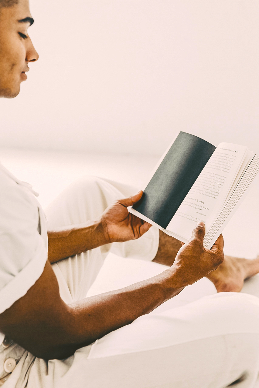 A shot of a patient reading a book in a white room at hollywood hills recovery house.