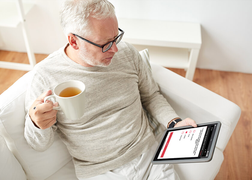 Male patient sitting at home on sofa filling out Scarletred ePRO on the tablet