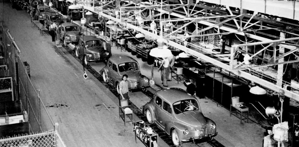 Black and white photo of a car assembly line.