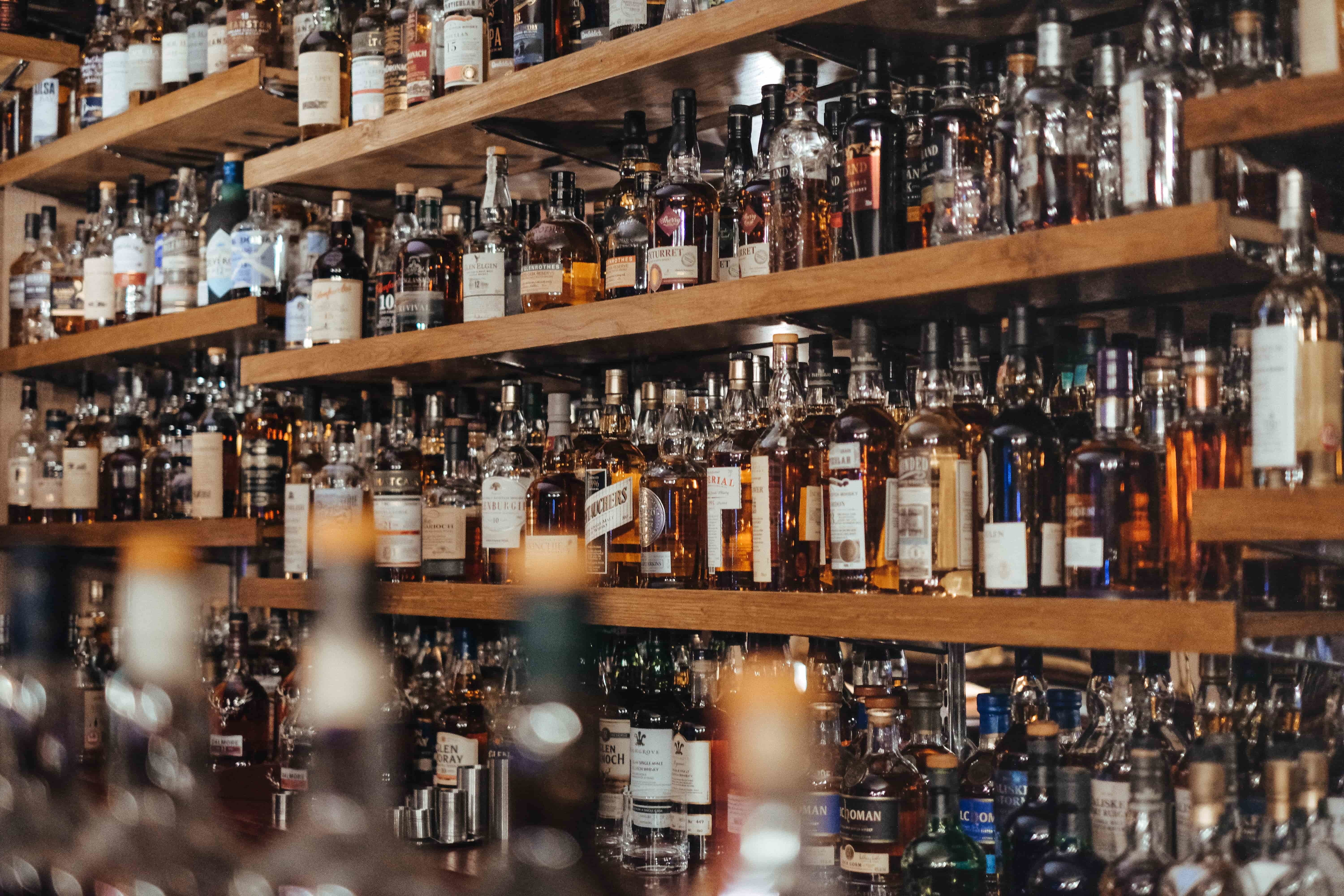 A lot of liquor bottles lined up on a bar
