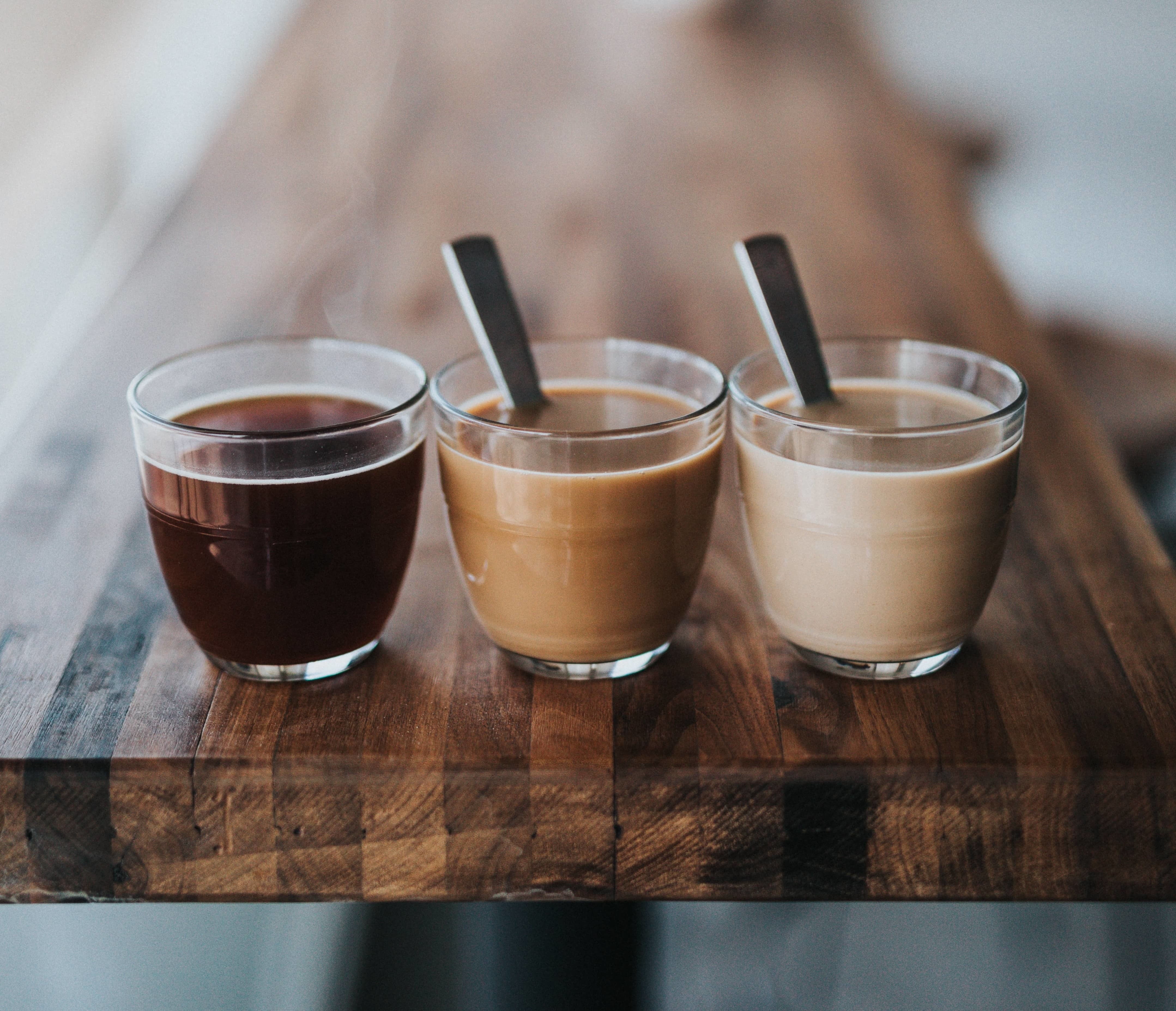 Three coffees on a tabletop.