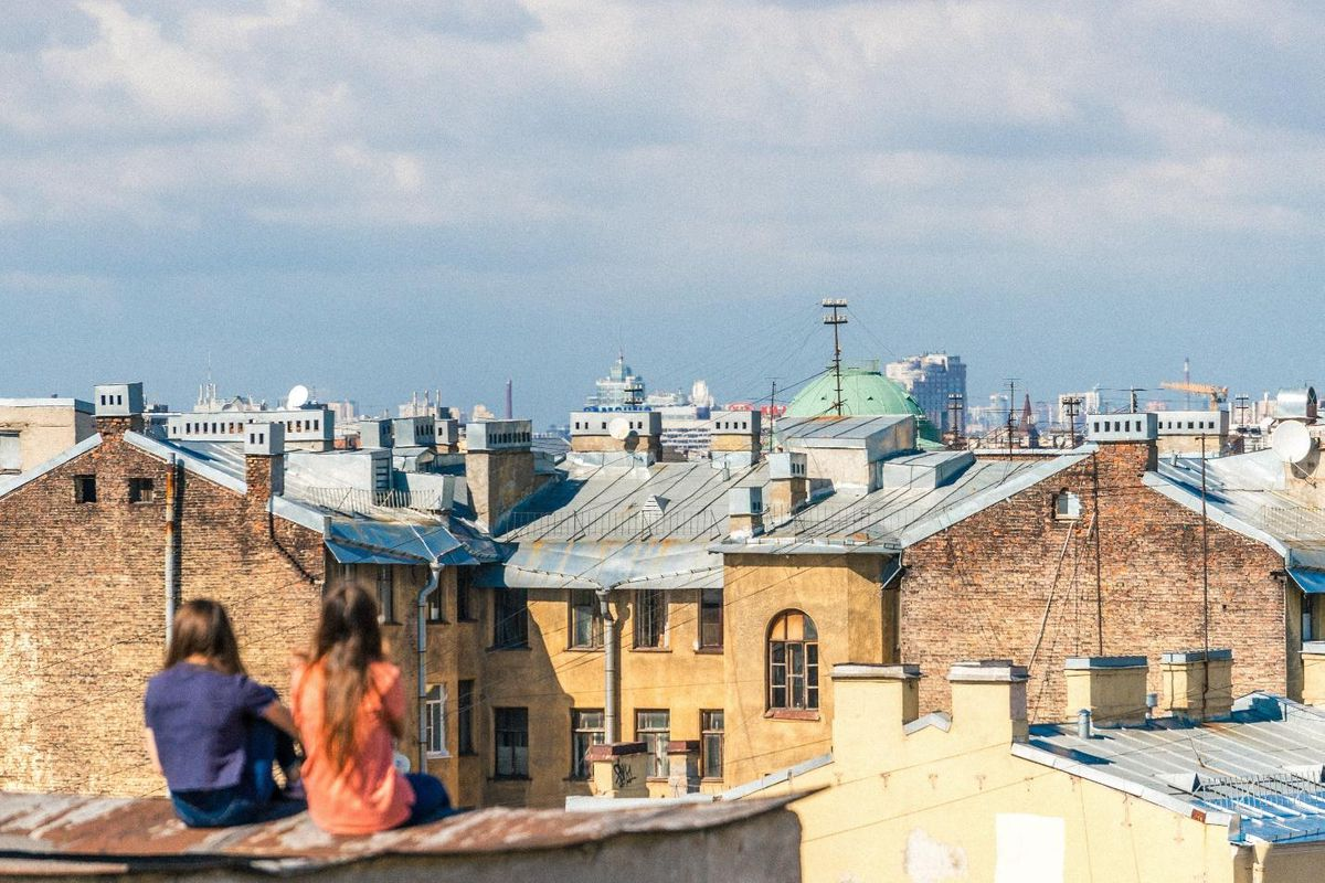 roofing contractors canadian two girls sitting on city rooftop