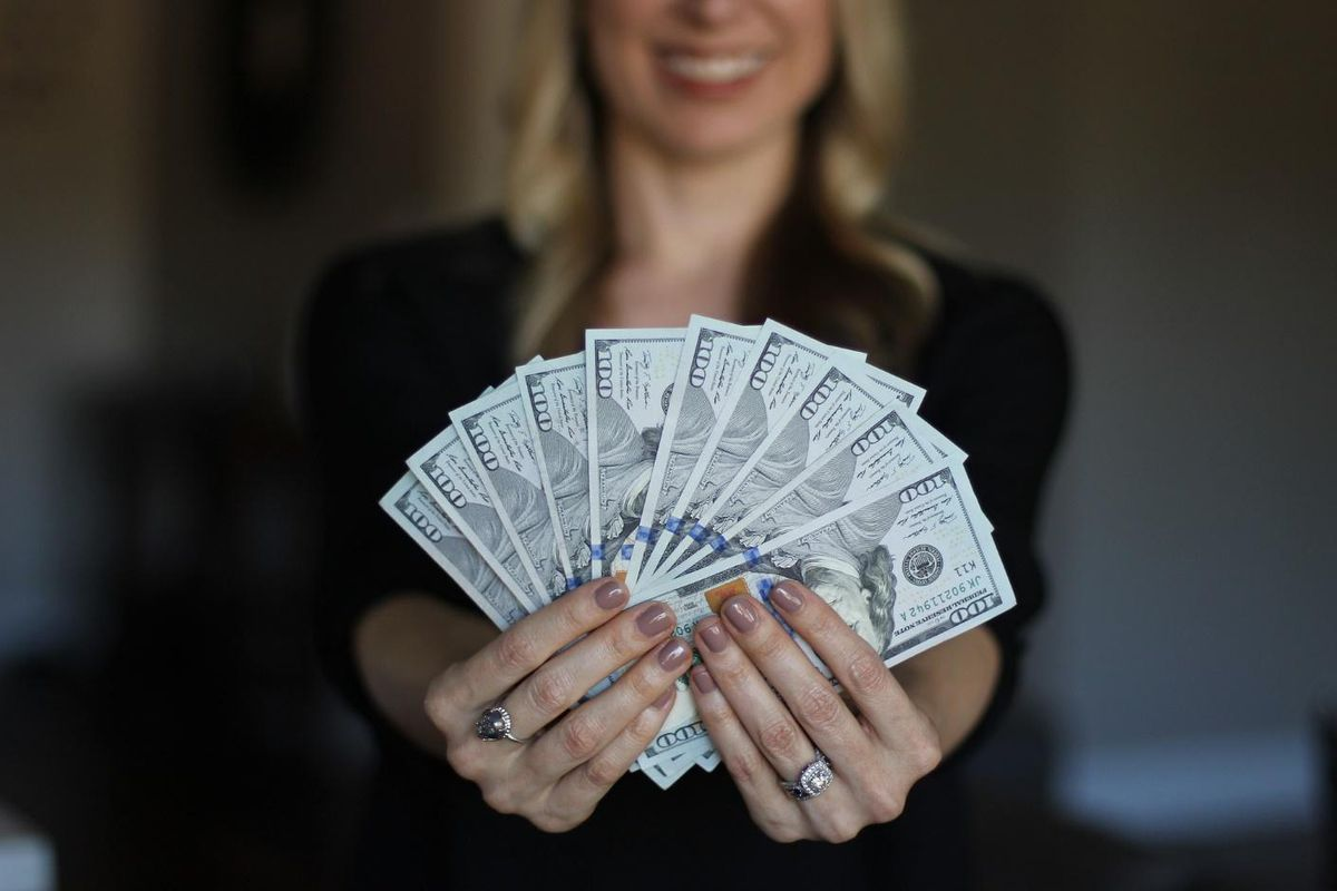 roofing companies woman holding fanned out stack of hundred dollar bills
