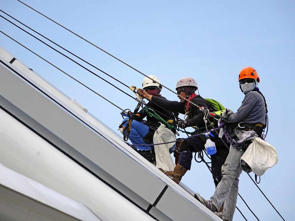 roofing supply men scaling roof with cables