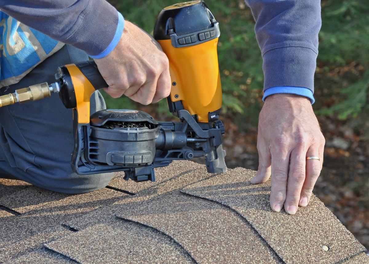 roofing supply man securing shingles with nail gun