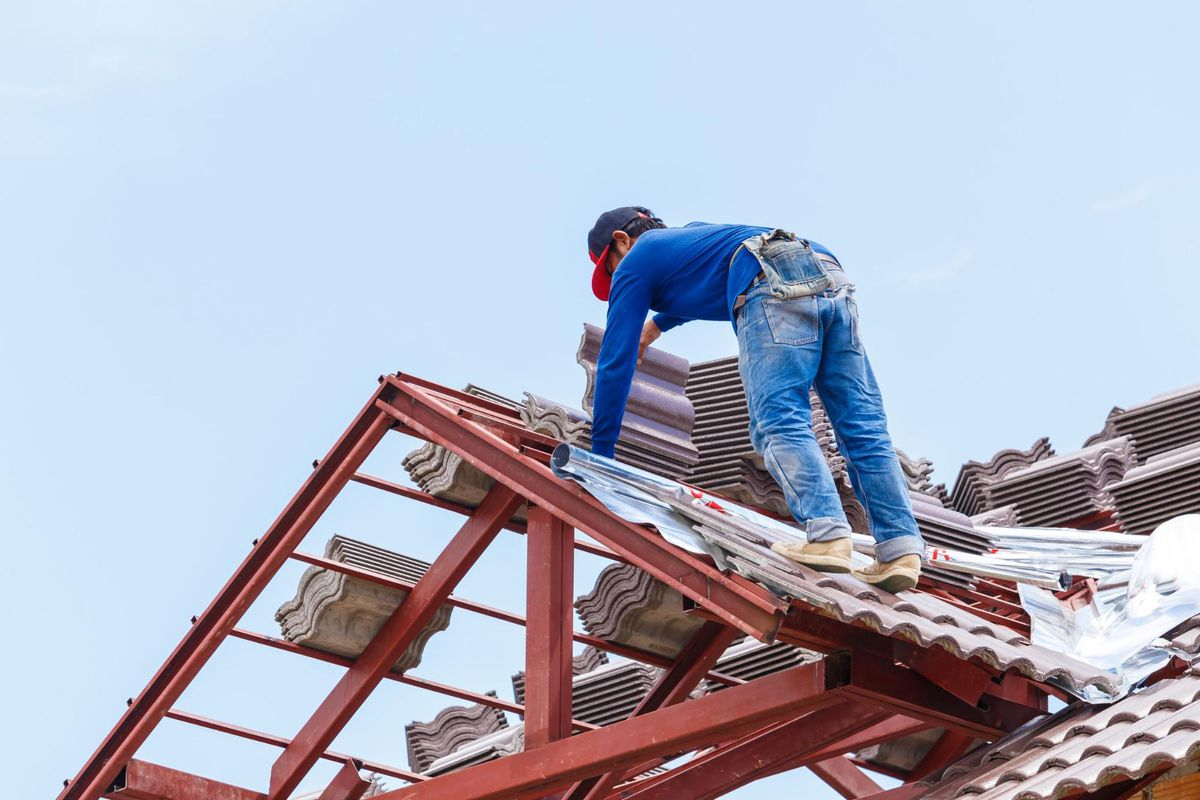 a roofr worker laying tile on roof frame