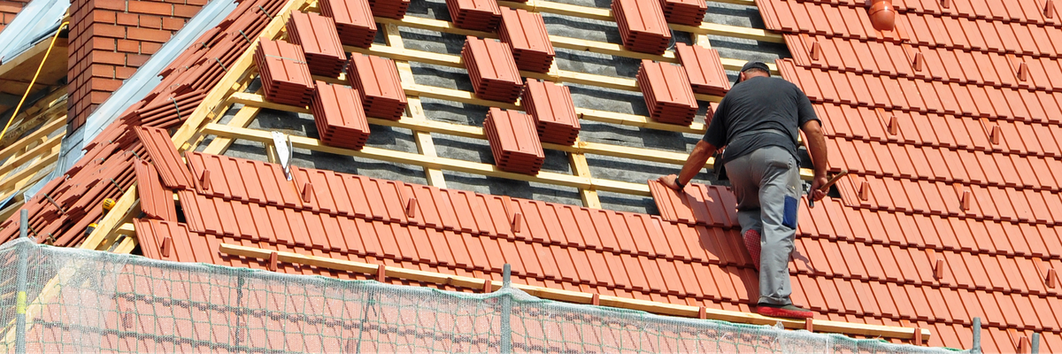 a roofr man laying tile roofing shingles on roof