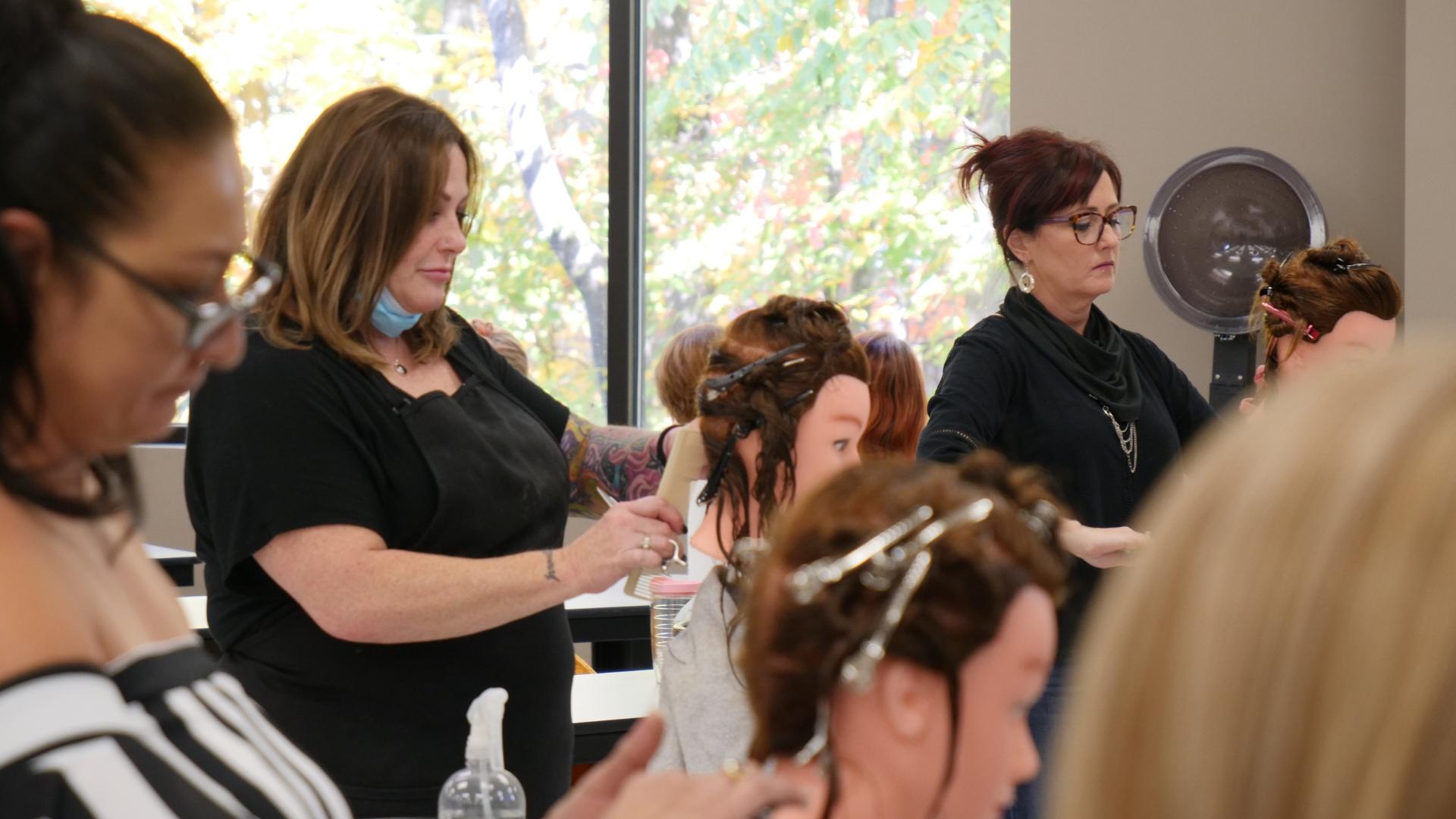 A woman cutting a mannequin head at a Franco Marino Coastline Education Salon Education