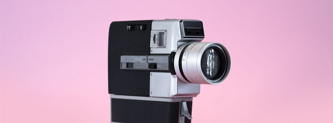 Antique video camera on a pink background