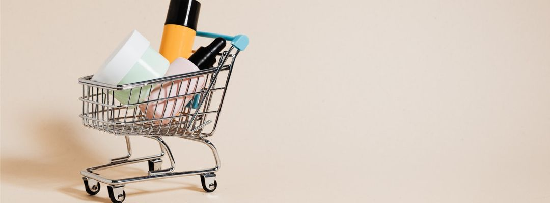 Mini shopping cart filled with large skincare products