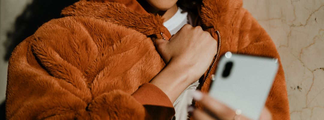 Woman wearing an orange puffy fur coat holding her phone