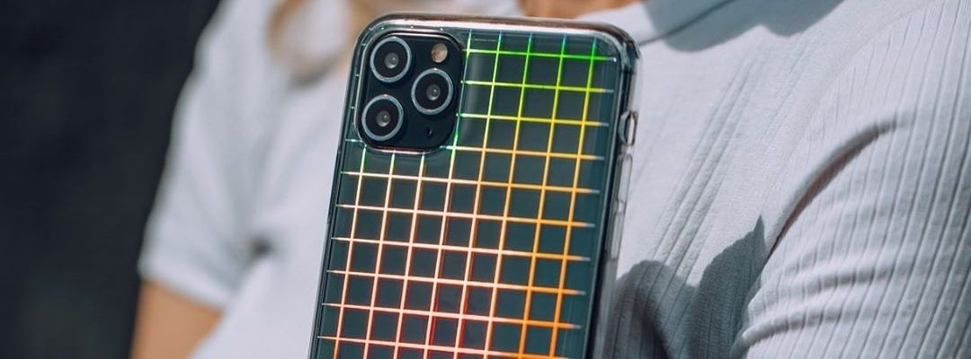 Person holding up an iPhone with a colourful checkered case