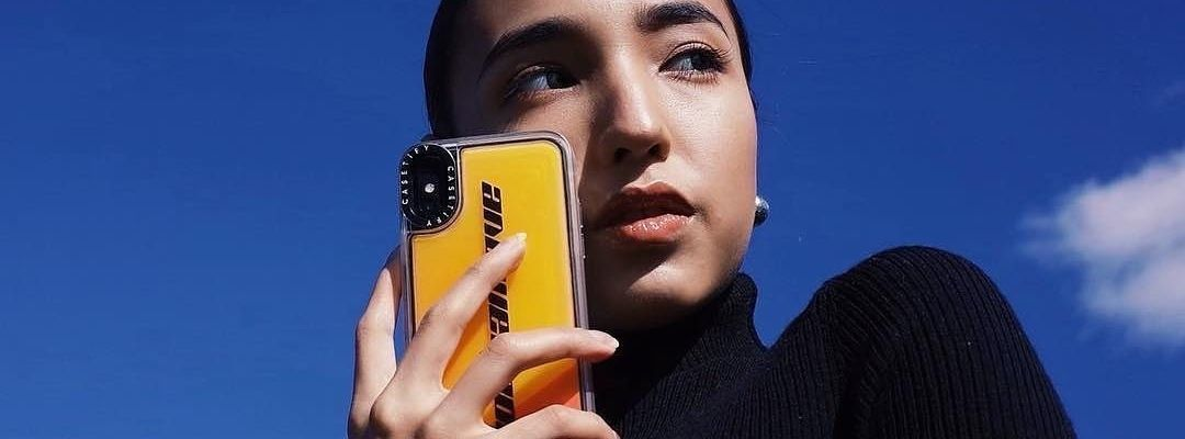 Model posing with a neon yellow iPhone case