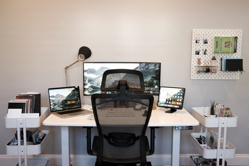 Home office setup including desk, chair, laptop and extra monitors