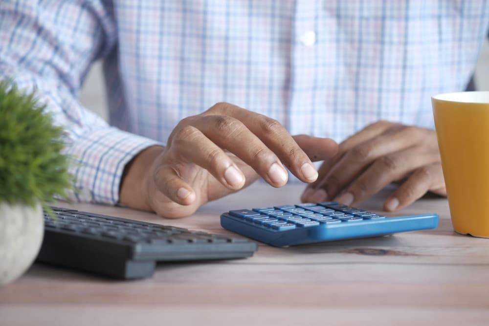 Person using calculator on their desk next to keyboard