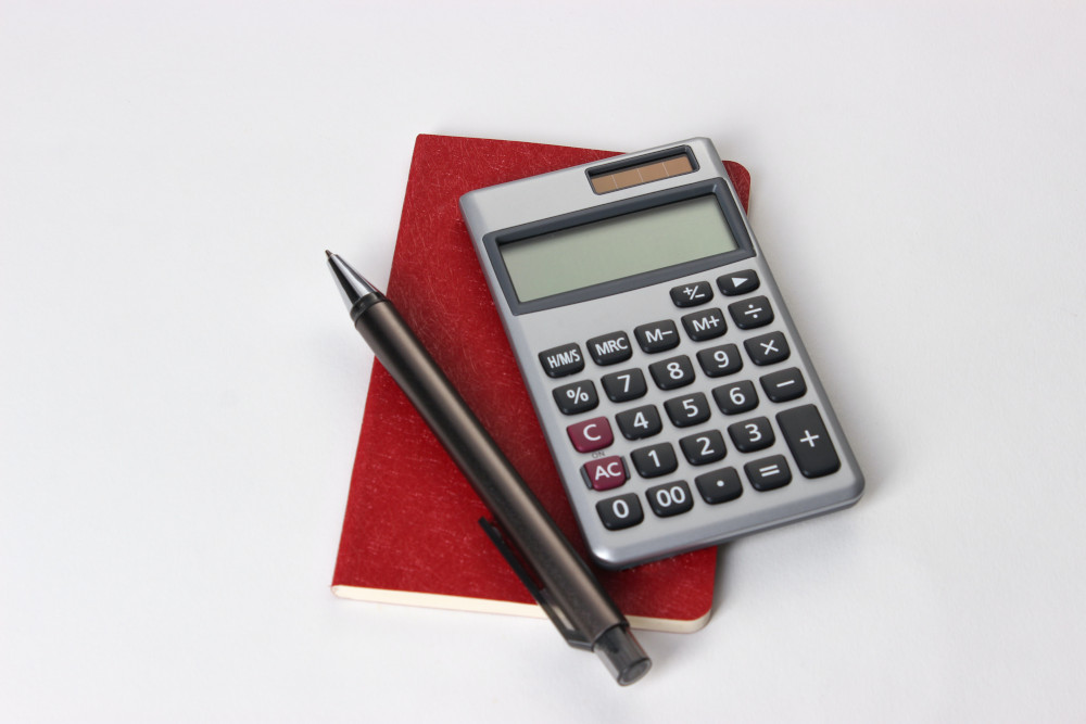 Calculator, notepad, and pen on a white surface