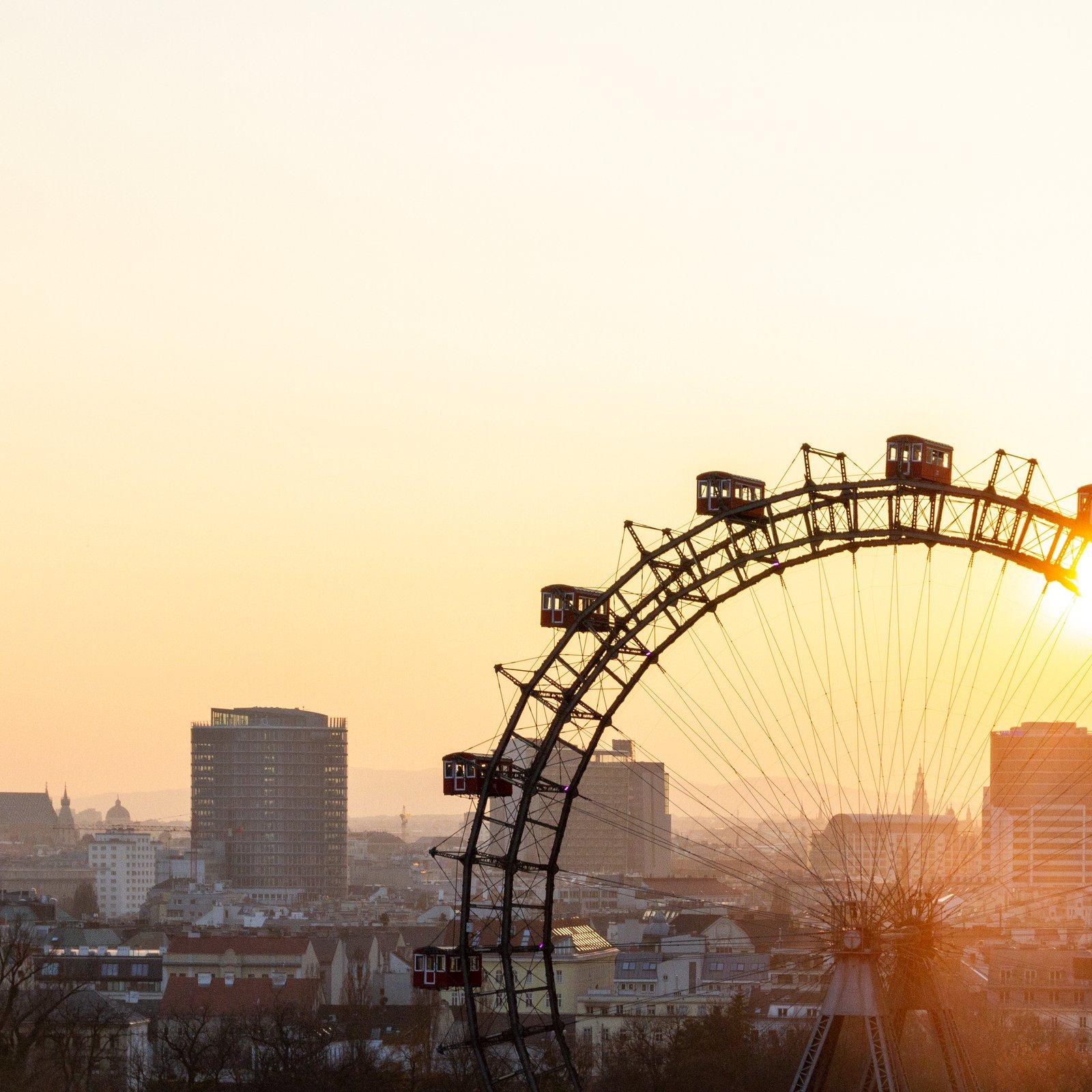 ferris wheel near city buildings during sunset