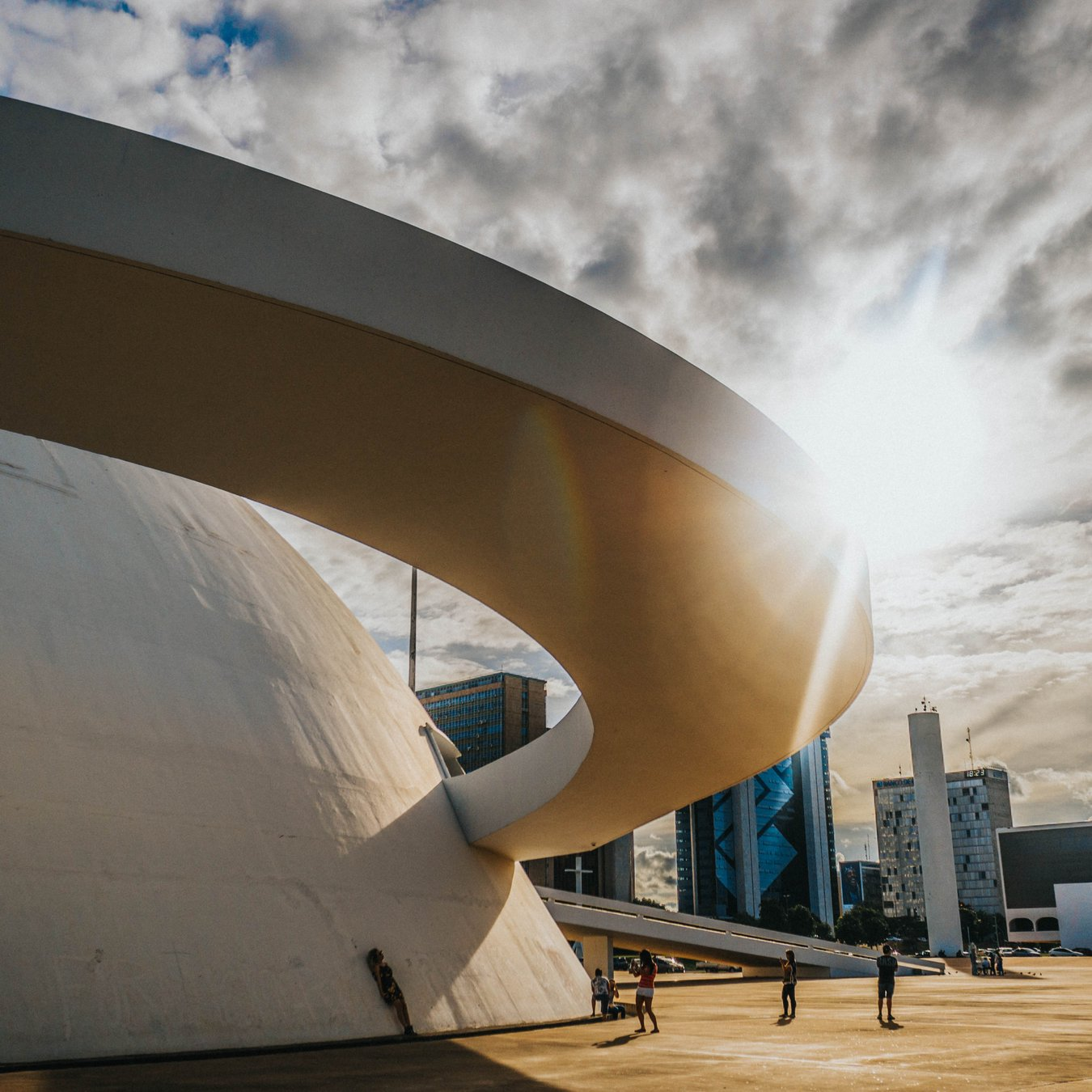 people walking on park near white concrete building under gray clouds during daytime