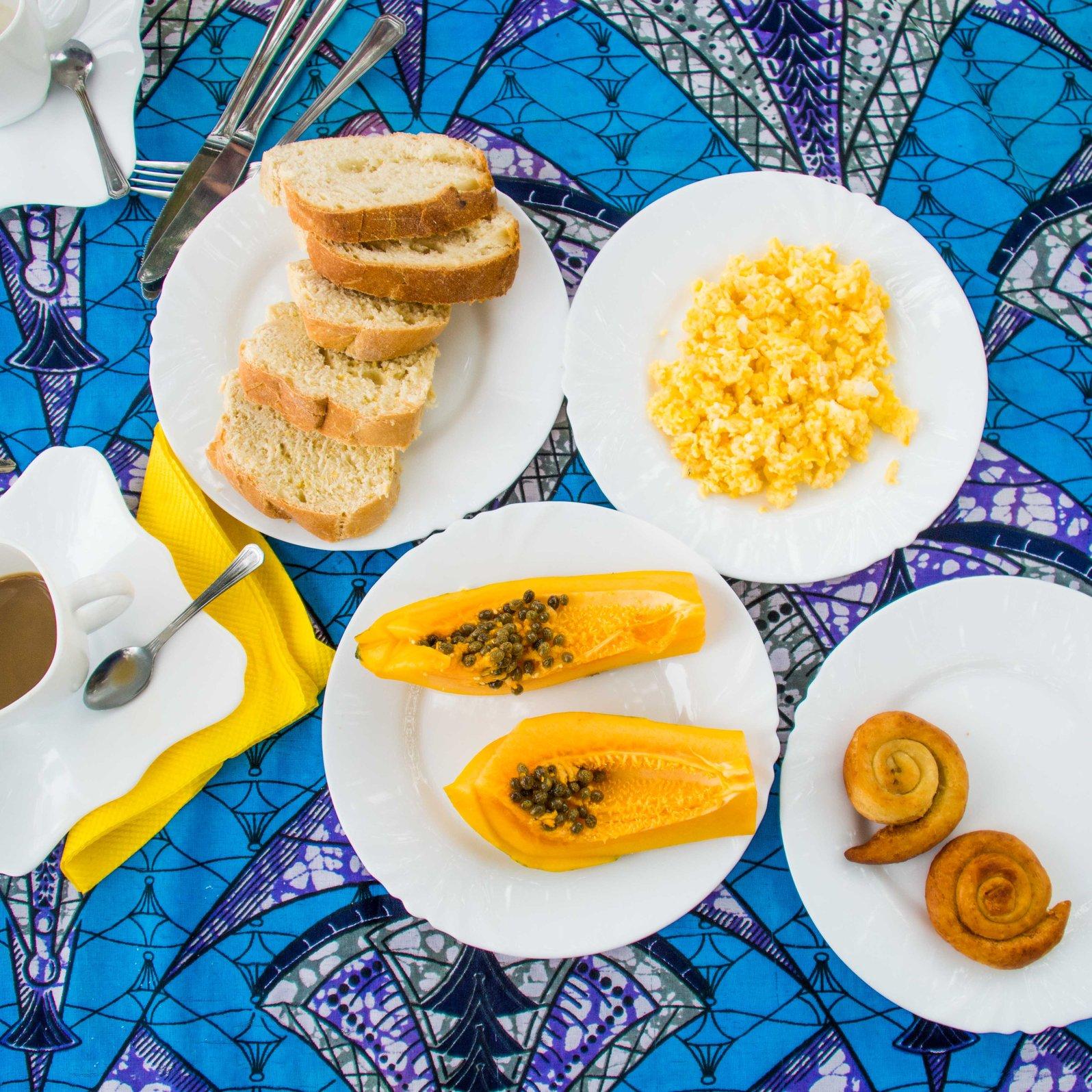 sliced papaya fruits, scramble egg, loaves of bread on white ceramic plates