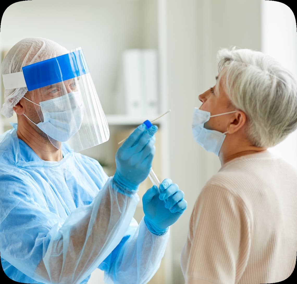 Elderly woman receives a covid-19 test from a man in a hazmat suit