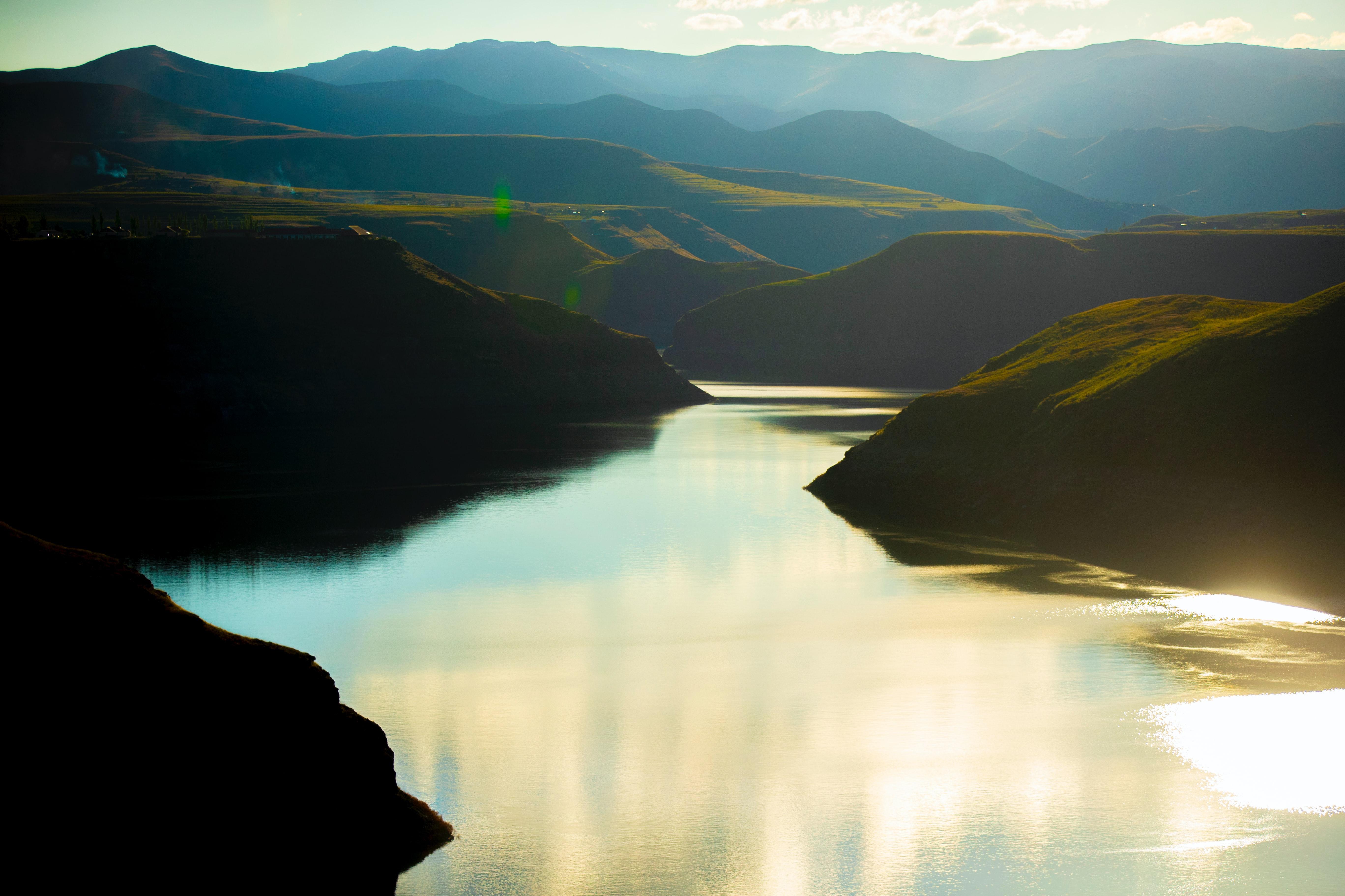 Green mountains beside lake during daytime