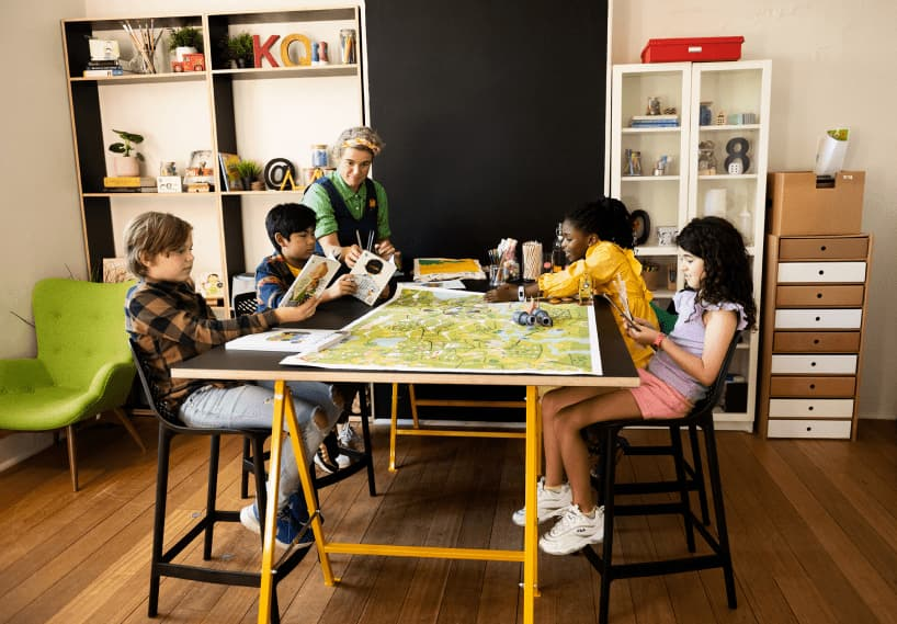 Image of Quirky Kid child psychology Sydney showing four children around a table doing craft with the help of child psychologist Dr Kimberley O'Brien