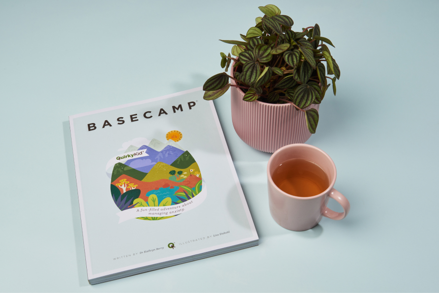 A cute image of the Basecamp Book by Quirky Kid next to a plant and a cup of team