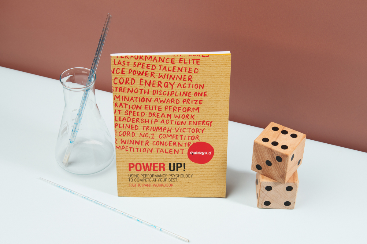 Image of the Power Up book by Quirky Kid next to a wooden dice and a lab jar.