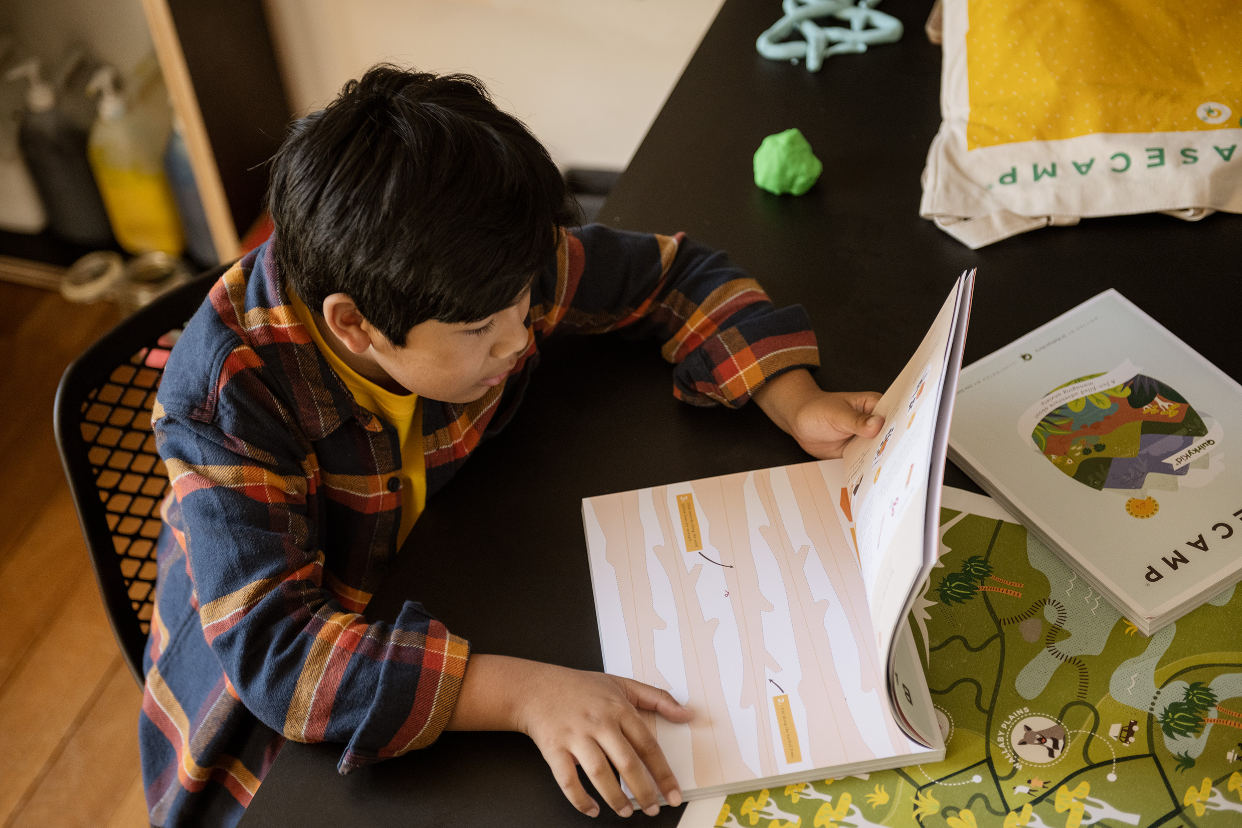 Image a a boy reading the basecamp anxiety book by quirky kid