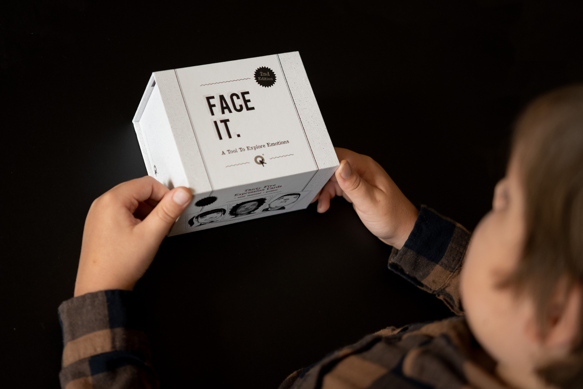 Product photography of the Face it Card with a boy just about to open the box